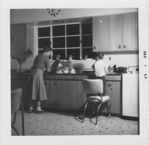 Mum and youngest brother in 1957 kitchen--note clock at top of photo, Dad made that as well!